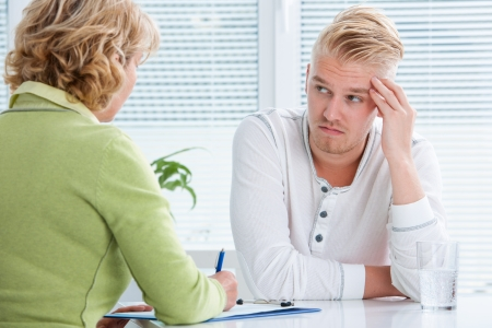 doctor exam: doctor talking to her male patient at office