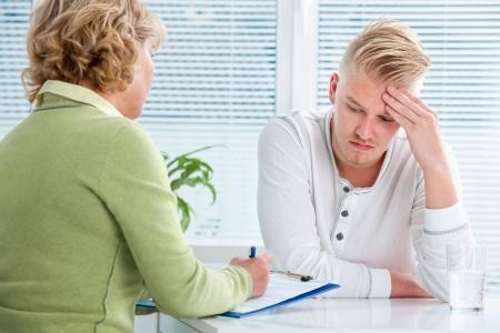 terapia psicologica: m?dico hablando con su paciente de sexo masculino en la oficina Foto de archivo