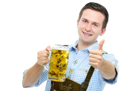 tracht: young man in traditional bavarian tracht holds Oktoberfest beer stein and shows thumb up Stock Photo