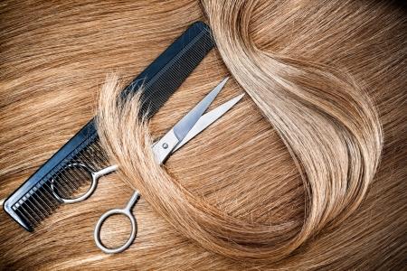 プロの美容師のはさみおよび背景髪に櫛