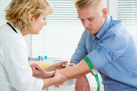 blood sample: Nurse taking blood sample from patient at the doctors office Stock Photo