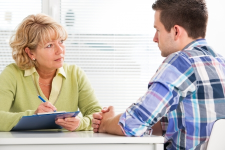counseling: Doctor talking to her male patient at office