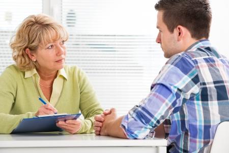 obrero trabajando: Doctora hablando con su paciente de sexo masculino en la oficina Foto de archivo