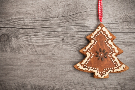 Gingerbread christmas tree hanging over wooden background photo