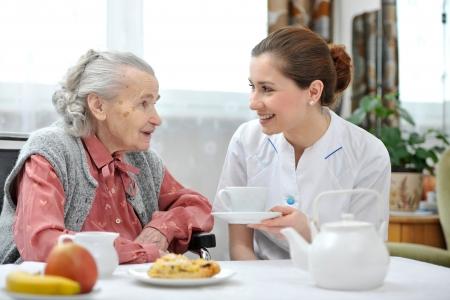 年配の女性は、退職後の家で昼食を食べる