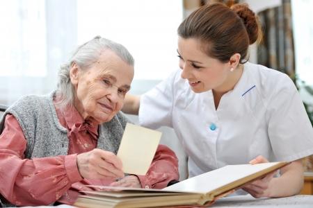 haushaltshilfe: Senior Frau und Krankenschwester suchen gemeinsam an Album mit alten Fotografien