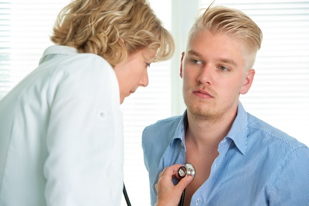 bronchitis: female doctor examining a young man in her office