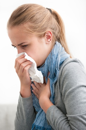 Portrait of a young woman sneezing In to tissue photo