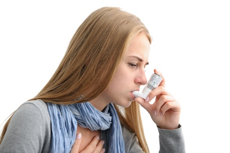 Jonge vrouw met behulp van een astma-inhalator als preventie