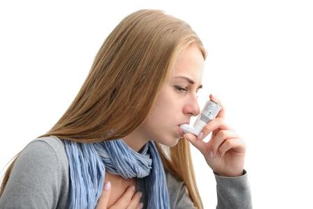 asma: Mujer joven usando un inhalador para el asma como la prevención Foto de archivo