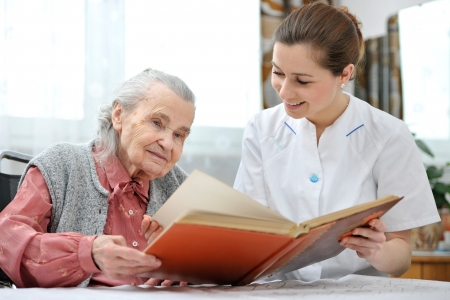 ancianos felices: Mujer mayor y enfermera mirando juntos en ?lbum con fotograf?as antiguas