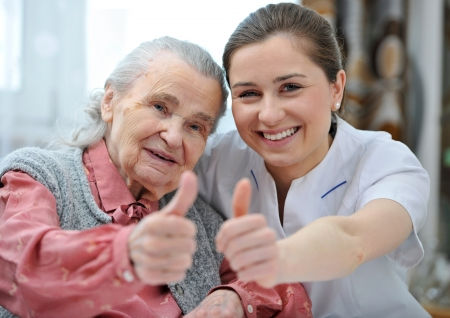 care at home: Senior woman and female nurse are showing thumbs up