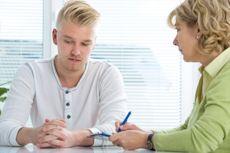 doctor burnout: Young man visits doctors office suffering with depression Stock Photo