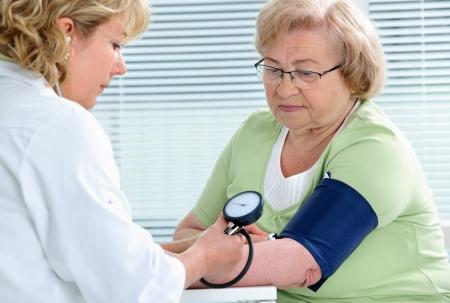 Doctor measuring blood pressure of senior patient photo