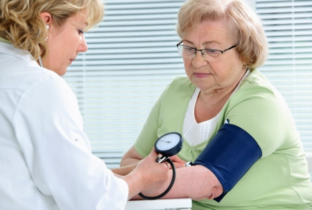 pressure: Doctor measuring blood pressure of senior patient Stock Photo