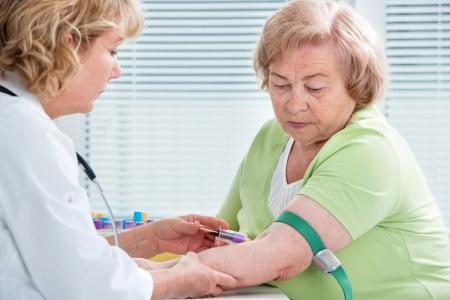 trekken: Verpleegster die bloedmonster van de patiënt bij de dokter Stockfoto