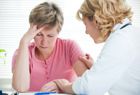 Mid adult woman talking to doctor about her diagnosis