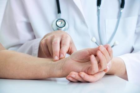 Doctor hands feeling pulse on male wrist photo
