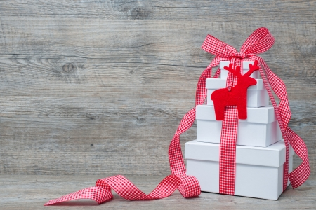 Stack of Christmas gifts with ribbon and bow  on old wooden background photo
