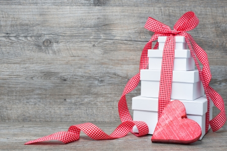 gift background: Stack of gift boxes with ribbon and bow  on old wooden background Stock Photo