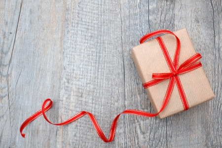 Gift box with red bow on wood background photo
