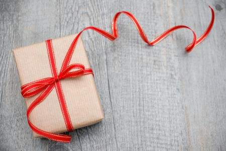 Gift box met rode strik op hout achtergrond Stockfoto
