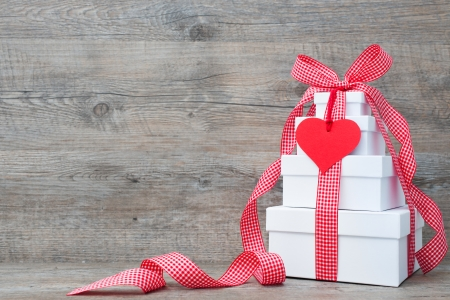 Stack of gift boxes with ribbon and bow  on old wooden background photo