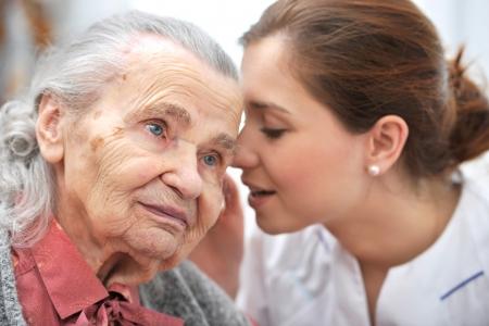 Vrouwelijke verpleegster spreekt in hogere vrouw oor
