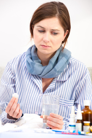 Sick young woman taking aspirin pills in bed Stock Photo - 22710180
