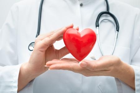 Vrouwelijke arts met de stethoscoop bedrijf hart