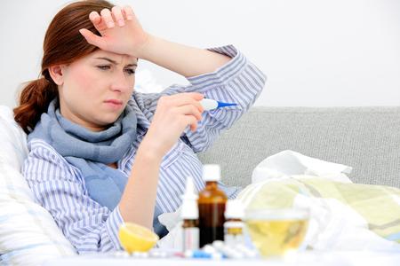 病気の女性は高熱とのベッドで横になっています。風邪、インフルエンザ、発熱と片頭痛