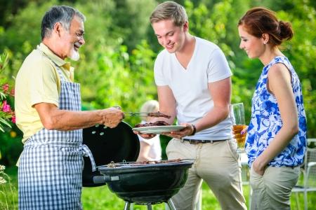 ライフスタイル: 夏のパーティーの彼らの庭でバーベキューを持っている家族