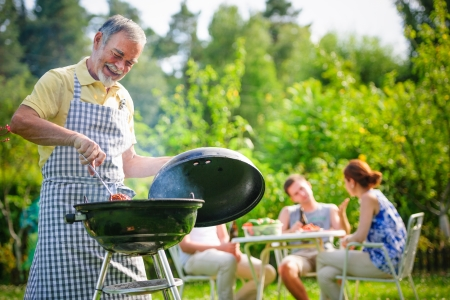 Famille ayant un barbecue dans leur jardin en été Banque d'images - 23487906