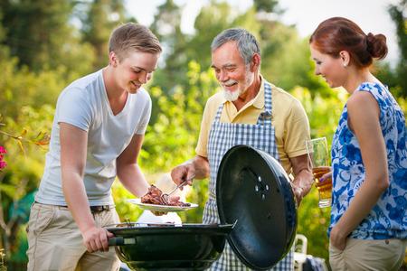 Familie met een barbecue feestje in hun tuin in de zomer Stockfoto