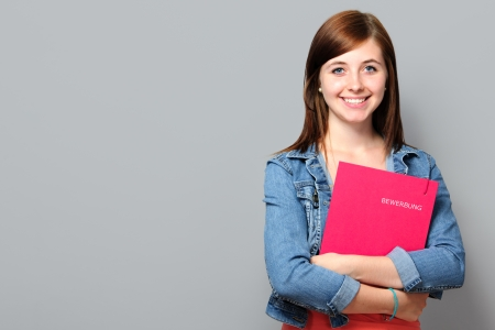 work book: Young woman holding job application on grey background Stock Photo