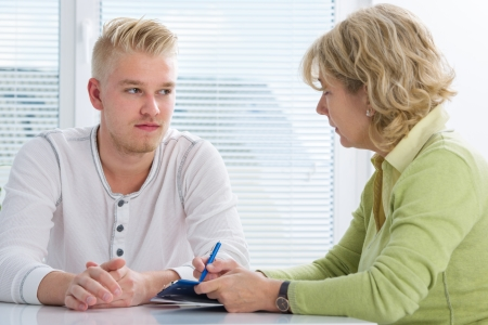 counseling: Teenager having a  therapy session while therapist is taking notes Stock Photo