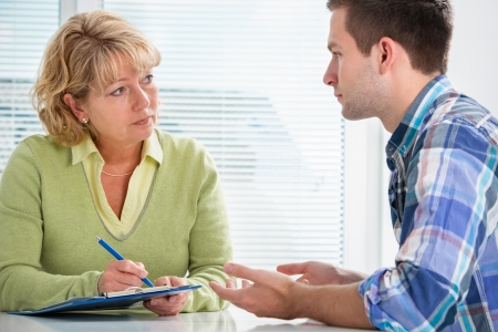consultation woman: Teenager having a  therapy session while therapist is taking notes Stock Photo