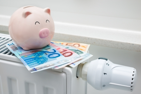 Heating thermostat with piggy bank and money, expensive heating costs concept photo