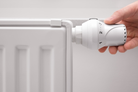 hand adjusting the temperature of heating radiator Banco de Imagens