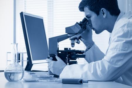 chimiste de sexe masculin travaillant avec un microscope dans un laboratoire