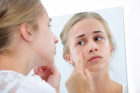 adolescencia: Adolescente comprobar su rostro para grano en el espejo