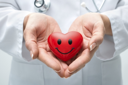 Female doctor with the stethoscope holding smiling heart Stock Photo