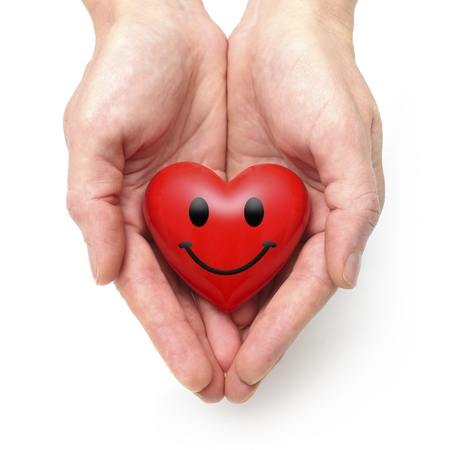 Smiling heart at the human hands isolated on white Stock Photo