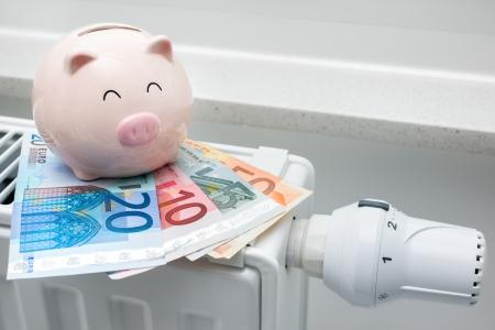 貯金箱とお金でサーモスタットを加熱、高価な暖房コスト概念