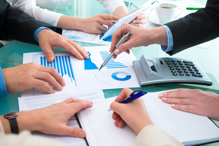 Closeup of human hands  over business documents at meeting photo