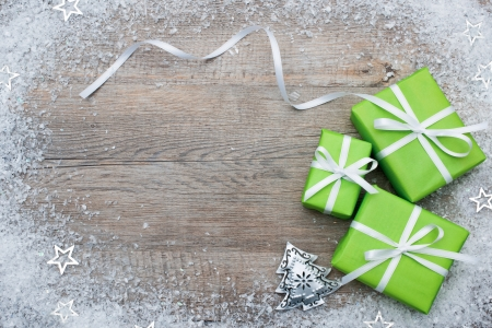christmastide: Gift boxes with bow and snowflakes on wooden background Stock Photo