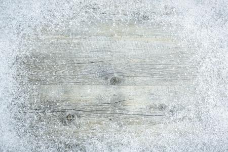 雪フレークで古い木の板。クリスマスの背景