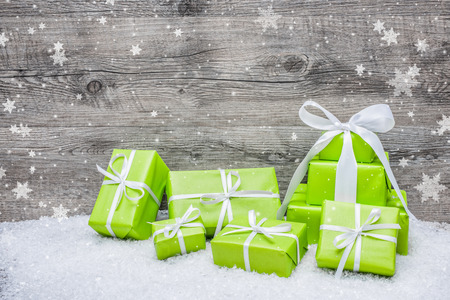 Gift boxes with bow and snowflakes on wooden background Stock Photo