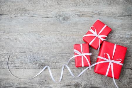 Contenitori di regalo con fiocco su sfondo di legno Archivio Fotografico - 24037451
