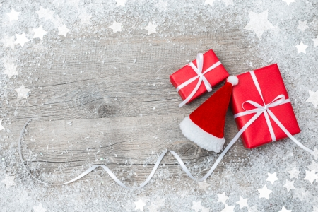 christmastide: Gift boxes with bow and Santa s hat on wooden background